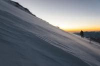 blurred climber at sunrise early morning walks on the slope and on the ground above the snow sweeps drifting snow