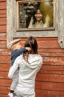 Rural scene with one year old baby boy with his mother outdoors looking at cottage window with grandmother inside