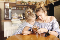 Happy mother and little girl having dinner and using smartphone at restaurant.