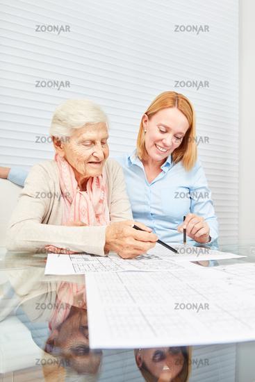 Junge Frau löst zusammen mit Seniorin Rätsel
