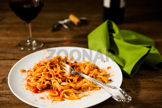 Half-eaten tagliatelle pasta with bolognese ragu and red wine