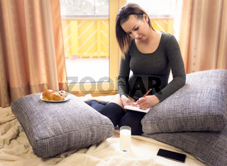 Attractive young woman writing on a notebook