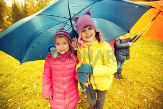 happy children with umbrella in autumn park