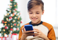 close up of happy boy with smartphone at christmas