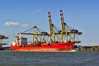 Frachtschiff vor Hafenanlagen und Kränen