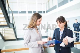 Zwei junge Geschäftsfrauen besprechen einen Bericht