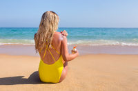 Girl on beach smearing sunscreen on skin