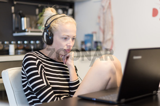 Adult woman in her casual home clothing working and studying remotely from her small flat late at night.