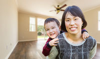 Chinese Mother and Mixed Race Child Inside Empty Room Of New House.