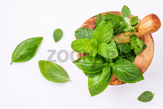 Alternative medicine fresh herbs in the wooden mortar . Food ingredients and seasoning basil, peppermint , dill and green mint  in a wooden mortar set up on white wooden background with copy space