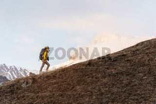A backpacker in a big fur hat and gloves with a backpack on his back goes uphill against the background of epic cliffs in the clouds. The concept of mountain tourism in any season
