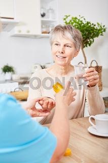 Frau gibt Arznei an Seniorin mit Alzheimer