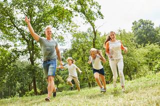 Glückliche Familie laufen über eine Wiese