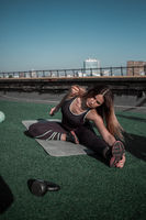 Attractive girl stretching on the roof.