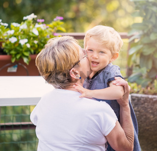 Grandmother hugs and gently kisses her grandchild in garden