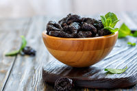 Dried black plums and mint in a wooden bowl.