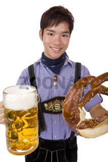Glücklich lachender Asiate hält Oktoberfest Mass und Breze