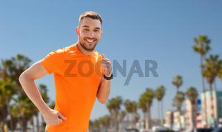 smiling young man running at summer seaside