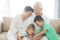 Grandparents and grandchildren using smart phones