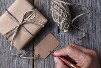 Man writing on a blank Christmas gift tag