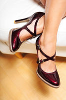 A woman's legs in cherry red  patent leather high heel shoes