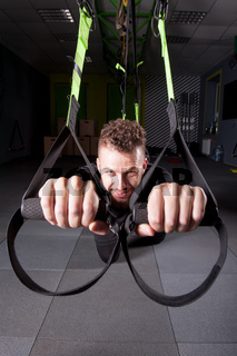 Handsome young muscled man training with trx while working out in gym