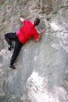 sportlicher Mann klettert an einer Felsenwand