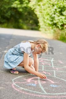 Mädchen malt ein Hüpfspiel auf den Boden