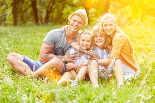 Glückliche Eltern und zwei Kinder im Garten
