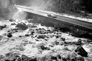Sports car driving on old stone bridge crossing river rapids.