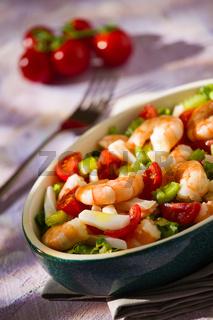 Salad of shrimps inside an oval bowl