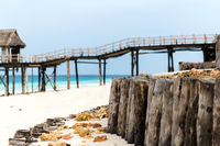 stilt bridge to bungalow hut on tropical beach