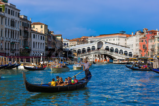 VENICE, ITALY - AUGUST 21, 2016: Tourists ride in gondola near Rialto bridge on August 21, 2016 in Venice Italy