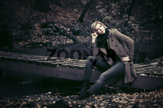 Young fashion blond woman in autumn forest