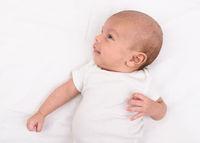 Newborn baby on white sheet