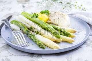 Codfish Fillet with green and white Asparagus and boiled Potatoes as top-view on a plate