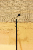 a lonely street lamp and its shadow on the wall of the house, painted with beige plaster.
