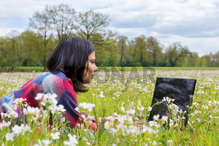 Woman with laptop lying in grass with flowers