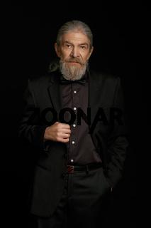 Old man in dark clothes on black background.