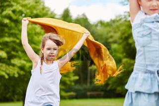 Mädchen läuft mit einem wehenden Tuch