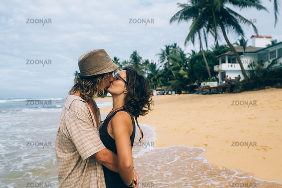 a guy and a girl are kissing on a beach