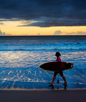 Woman surfer at sunset. Bali