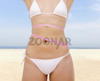 Bikinifigur: Frau im Bikini misst Hüftumfang am Strand mit Maßband