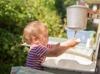 Boy washes his hands outdoors