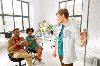man showing scheme to creative team at office
