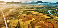 Aerial view of a hot air baloon over rice fields in rocky mountain valley and river