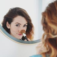 mirror portrait of a young woman powdering her nose