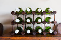 white wine bottles stored on wooden rack
