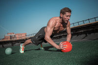 Sporty man using ball to work out on abs and shoulder muscles.