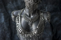 handmade piece, silver jewelry costume with chains and coins. wears a headdress made with feathers and gothic pieces